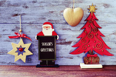 Rustic christmas ornaments and text seasons greetings. A chalkboard in the shape of Santa Claus with the text seasons greetings against a blue rustic wooden royalty free stock photo
