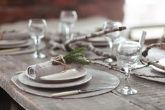 Rustic Christmas served wooden table with vintage silverware, candles and fir twigs. New Year Celebration, Christmas. Dinner served in loft interior Royalty Free Stock Photography