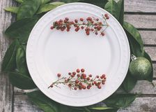 Rustic Christmas setting with red berries royalty free stock photo