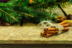 Rustic Christmas wooden background with cinnamon sticks and fir tree. Stock Image