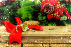 Rustic Christmas wooden background with red bow and gold bell Royalty Free Stock Images