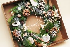 Rustic Christmas wreath with green fir branches, pinecones, natural elements. Wraped in craft box, gift box royalty free stock photos