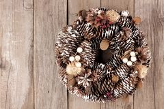 Rustic Christmas wreath of pine cones over aged wood Stock Photography