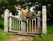 Rustic Church Gate. Autumnal view of a Medieval English Church looking through a pair of rustic gates Stock Photo