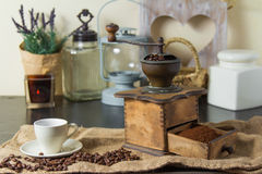 Rustic coffee grinder in kitchen. Simple rustic coffee grinder tool with grounds and beans on burlap cloth in front of lantern, plant and mug Stock Photos