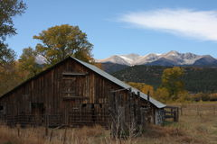 Rustic Colorado Barn with Mountains in the back Ground Royalty Free Stock Photos