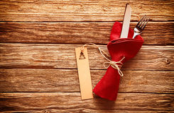 Rustic colorful red Christmas place setting. With cutlery wrapped in a red napkin with a gift tag decorated with an Xmas tree on a wooden table with copyspace royalty free stock photos