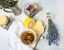 Rustic composition of tea, lavender, lemon and textile on concrete eco background. Royalty Free Stock Images