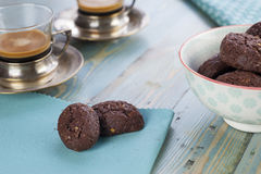 Rustic cookies with chocolate and nuts in ceramic bowl. With two cups of espresso and cloth napkins Royalty Free Stock Photos