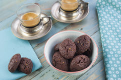 Rustic cookies with chocolate and nuts in ceramic bowl. With two cups of espresso and cloth napkins Royalty Free Stock Photo