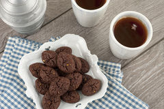 Rustic cookies with chocolate and nuts in ceramic bowl. With two cups of tea, sugar and cloth napkins Stock Photos