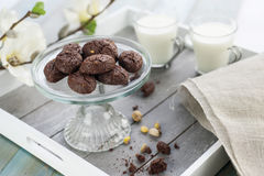 Rustic cookies with cocoa and pistachio nuts on cake-stand. For sweets with wooden tray two cups milk, cloth napkin and white flowers in the background Stock Images