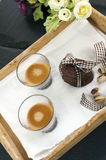 Rustic cookies with cocoa and pistachio nuts on wooden tray. Single and stacked tied with cloth ribbon, cup of espresso coffee, cloth tablecloth and white Royalty Free Stock Images