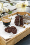 Rustic cookies with cocoa and pistachio nuts on wooden tray. Single and stacked tied with cloth ribbon, cup of espresso coffee, cloth tablecloth and white Royalty Free Stock Photo