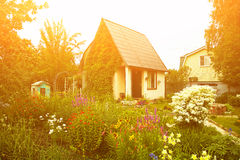 Rustic country house in the lush garden Stock Image
