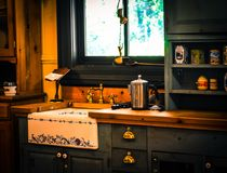 Rustic country kitchen. Interior of ceramic sink in rustic country kitchen with wood cabinets and butcher block counters Stock Images