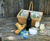 Rustic country picnic setting. Close up image of a rustic country picnic for two with wine, fresh bread and cheese in a ceramic container on a wooden background Royalty Free Stock Images