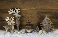 Rustic country style decoration with reindeer, lantern and snow Royalty Free Stock Photo