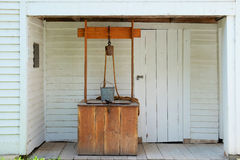 Rustic Country Well. Rustic wooden country well with metal bucket and rope on pulley stock photo