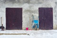 Rustic countryside house. Old countryside wall with two wooden doors and wheelbarrow Stock Image