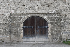 Rustic cracked wall with old wooden door. Stone texture Stock Image