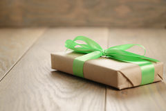 Rustic craft paper gift box with green ribbon bow on wood table stock images