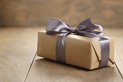 Rustic craft paper gift box with lilac ribbon bow on wood table. Shallow focus royalty free stock photos