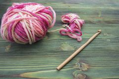 Rustic crochet thread and a bamboo hook. Warm pink winter yarn ball for knitting and crochet on the wooden table. Rustic backgroun Stock Image