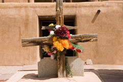 Rustic cross with flowers. Rustic cross with artificial flowers against adobe background Stock Photos