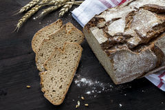 Rustic crusty bread and slices on a dark brown wooden table Royalty Free Stock Photography
