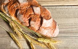 Rustic crusty bread and wheat ears on a dark wooden table Royalty Free Stock Photos