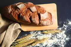 Rustic crusty bread and wheat ears on a dark wooden table Stock Photos
