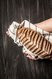 Rustic crusty loaf of bread in baker `s hands on black Stock Photo