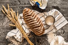 Rustic crusty loaf of bread and ingredients on black Stock Photography