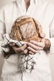 Rustic crusty loaf of bread in baker man`s hands royalty free stock images