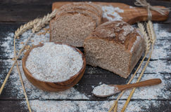 Bakery Bread on a Wooden Table. Rustic cut bread, flour on Wooden bowl, wheat and cutting board on vintage wood table Royalty Free Stock Photo