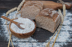 Bakery Bread on a Wooden Table. Rustic cut bread, flour on Wooden bowl, wheat and cutting board on vintage wood table Royalty Free Stock Images