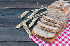 Bakery Bread on a Wooden Table. Rustic cut bread, wheat and cutting board and picnic cloth on vintage wood table. Copy space Royalty Free Stock Image