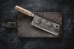 Rustic Cutting Board and Meat Cleaver on Dark Background. Butcher Shop Tool stock photo
