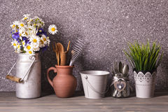 The rustic decor. Bouquet of daisies in a vintage tin can, gray bucket and rough ceramic jug with wooden cooking utensil set royalty free stock photography