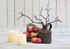 Rustic decoraton with apples, candles and twigs in a vase on a white wooden background Royalty Free Stock Images