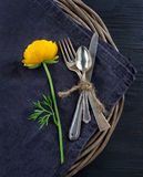 Rustic dinner setting with with a yellow flower. Rustic dinner setting with dark napkin and yellow flower on black wooden table stock images