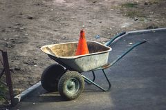 Rustic dirty construction wheelbarrow with push broom on the street. Orange road construction cone in the background Stock Photo