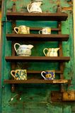 Rustic display of pottery. Pottery for sale in Italian village, on a rustic shelf with green background Stock Photo