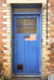 The rustic door. Rustic door with cats door flap on the brick wall, patched, with paint coming off. English countryside stock photography