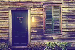 Rustic door and window with closed shutters and porch light Stock Image
