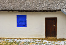 Traditional romanian house. Facade with roof, blue window and wooden door Royalty Free Stock Photography