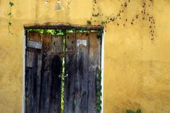 Rustic door, yellow wall, Antigua, Guatemala. Royalty Free Stock Image