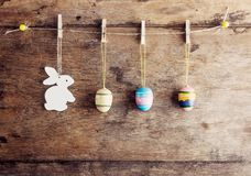 Rustic Easter background: Vintage painted eggs and white bunny hang on clothespins against old brown wooden wall. Holiday concept royalty free stock images