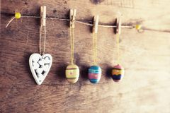 Rustic Easter background: Vintage painted eggs and white heart hang on clothespins against old brown wooden wall. Holiday concept stock images